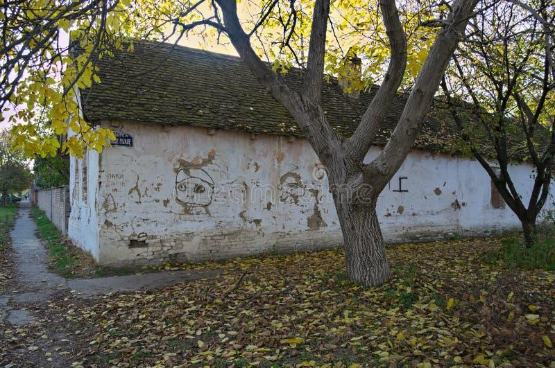 Vieille maison abandonnée aux carrefours, et arbres avec les feuilles sèches tombées autour photo libre de droits