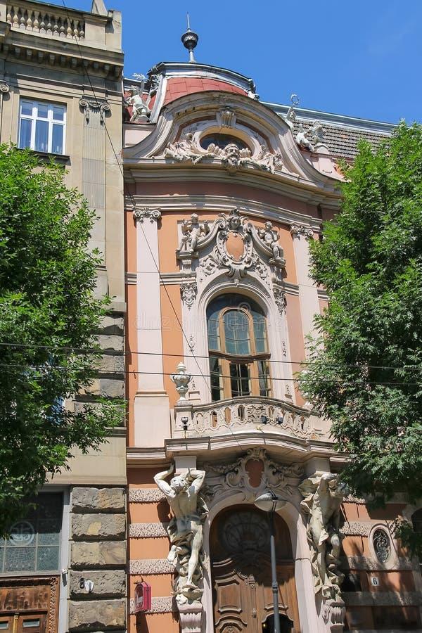 Vieille maison avec des anges sur le toit et l'atlas des deux côtés images libres de droits