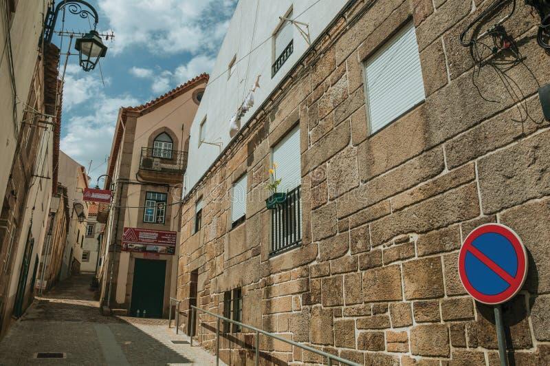 Vieille maison avec le mur en pierre sur l'all?e et le panneau routier de STATIONNEMENT INTERDIT images stock