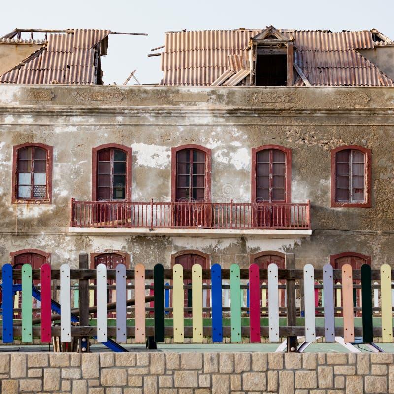 Vieille maison avec le toit cassé et la barrière très colorée images stock