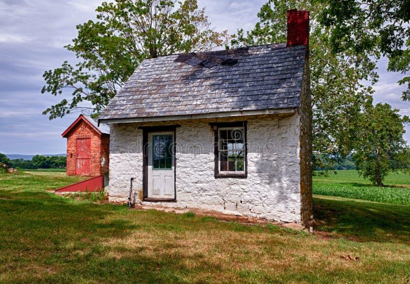 Vieille maison blanche sur des terres cultivables photos stock