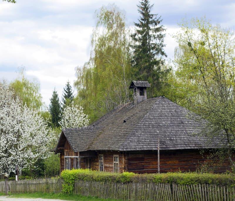 Vieille maison en bois avec le toit en bois dans le village près des arbres de fleur photographie stock