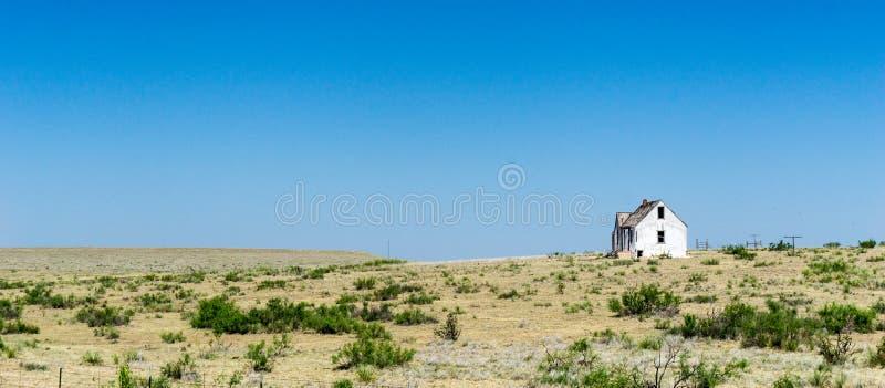 Vieille maison en bois blanche délabrée et abandonnée sur la prairie à distance dans le middlew de nulle part sous un ciel bleu images libres de droits