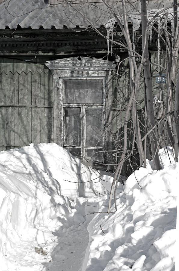 Vieille maison en bois dans la fenêtre sibérienne de village couverte de neige photo libre de droits