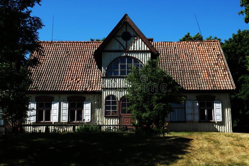 Vieille maison en bois entourée par des arbres photos stock