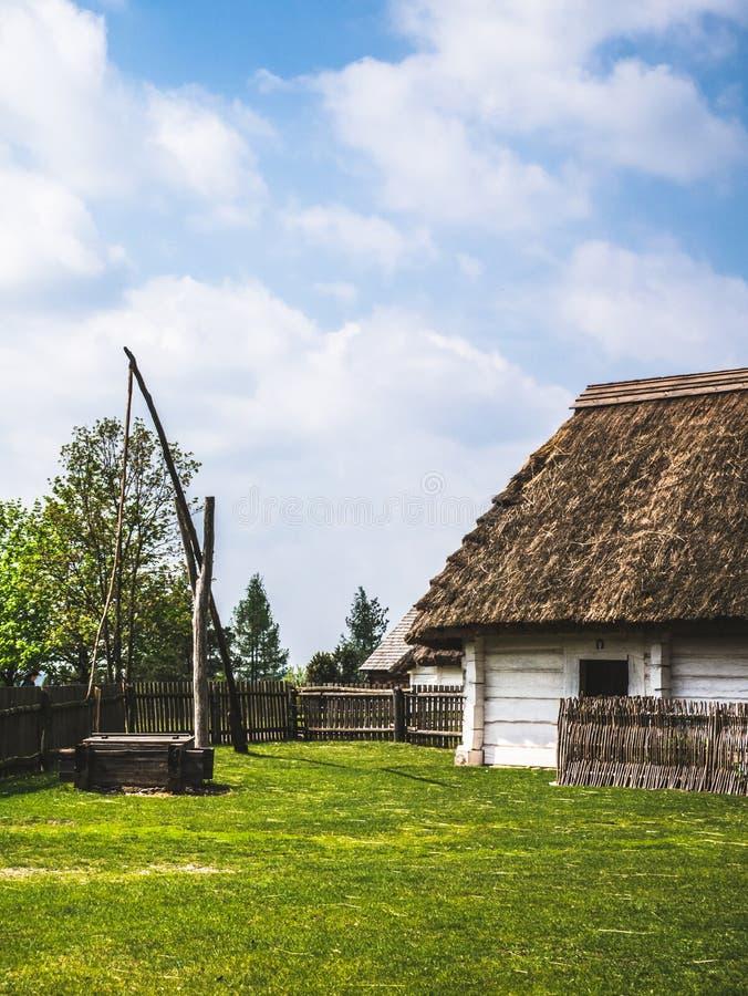 Vieille maison en bois et un puits dans la campagne photo libre de droits
