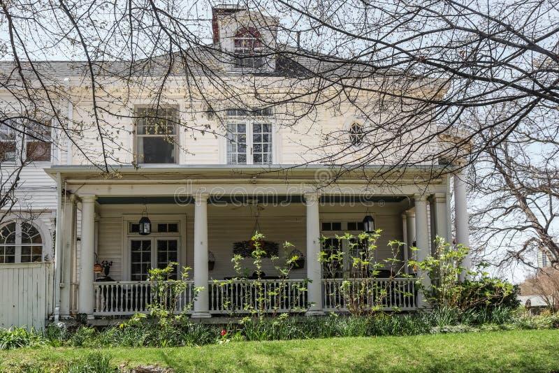 Vieille maison en bois majestueuse mais minable en premier ressort avec les branches et les fleurs de bourgeonnement commençant à images libres de droits