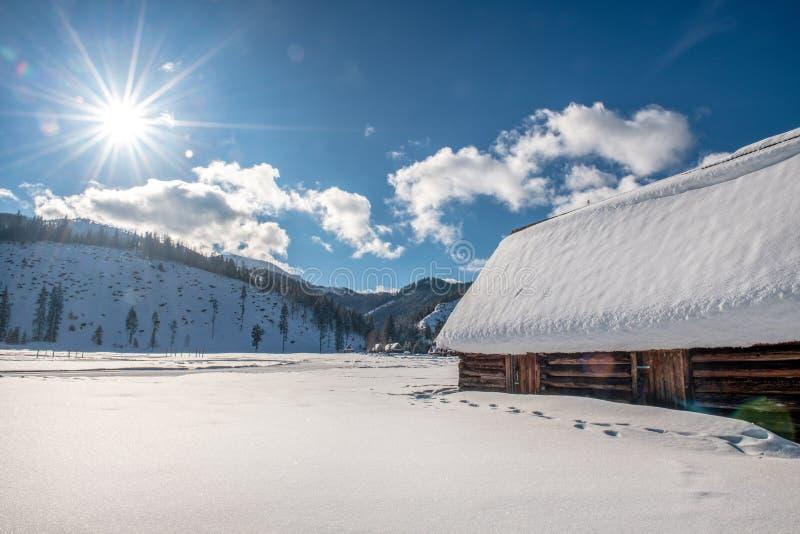 Vieille maison en bois par la route dans un beau paysage d'hiver Le soleil admirablement lumineux à l'arrière-plan photos stock