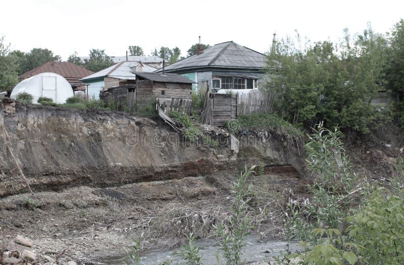 Vieille maison en bois ruinée au bord d'une falaise s'émiettant dangereusement la terre sur la berge dans un village sibérien image libre de droits