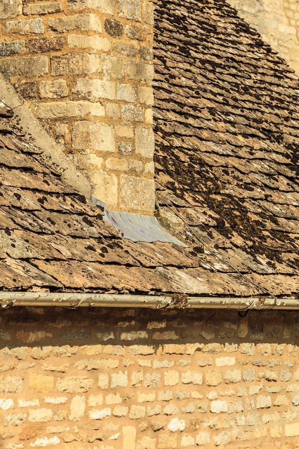 Vieille maison en pierre avec les tuiles de toit moussues de cheminée images libres de droits