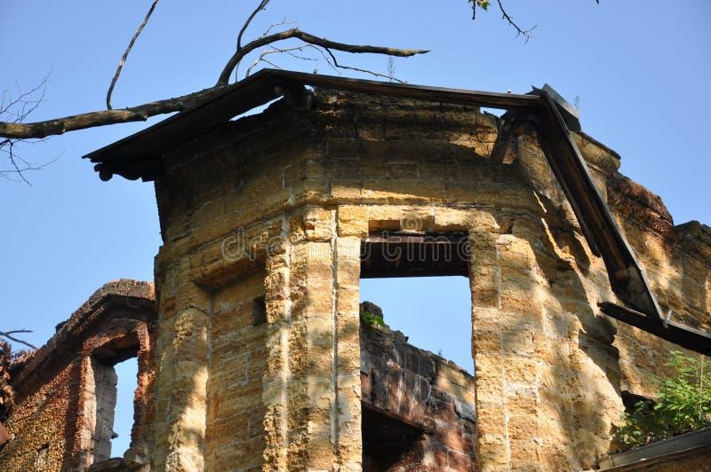 Vieille maison en pierre détruite jaune antique sur la cour avec des arbres autour Pauvreté et misère, du sud, été image stock