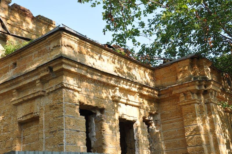 Vieille maison en pierre détruite jaune antique sur la cour avec des arbres autour Pauvreté et misère, du sud, été photo libre de droits