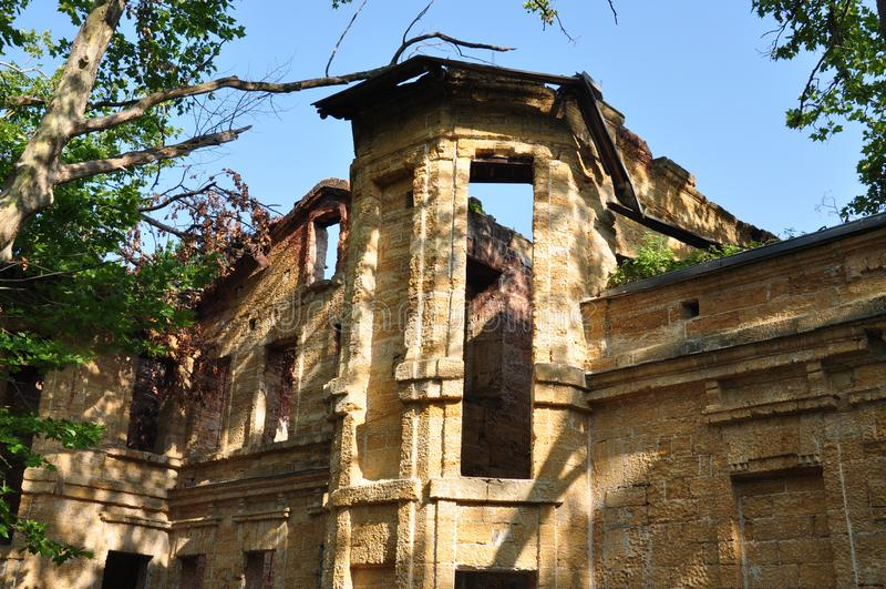 Vieille maison en pierre détruite jaune antique sur la cour avec des arbres autour Pauvreté et misère, du sud, été images libres de droits