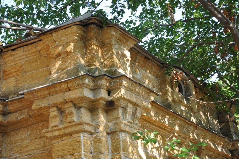 Vieille maison en pierre détruite jaune antique sur la cour avec des arbres autour Pauvreté et misère, du sud, été photographie stock libre de droits