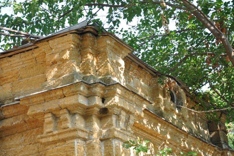 Vieille maison en pierre détruite jaune antique sur la cour avec des arbres autour Pauvreté et misère, du sud, été photos libres de droits