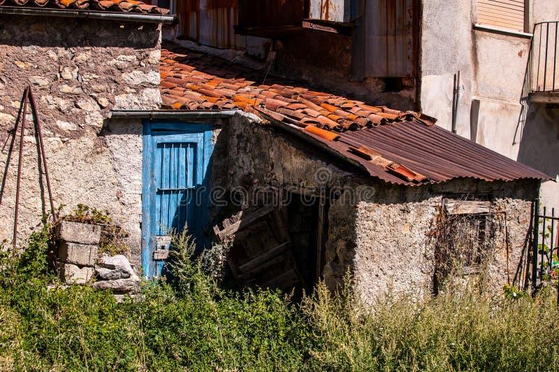 Vieille maison italienne dans le délabrement avec la porte bleue images stock