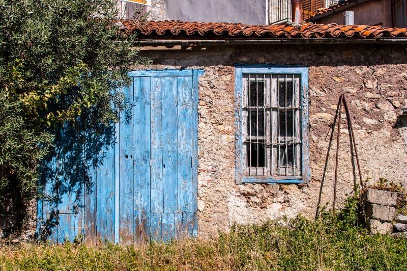 Vieille maison italienne dans le délabrement avec la porte bleue photos libres de droits