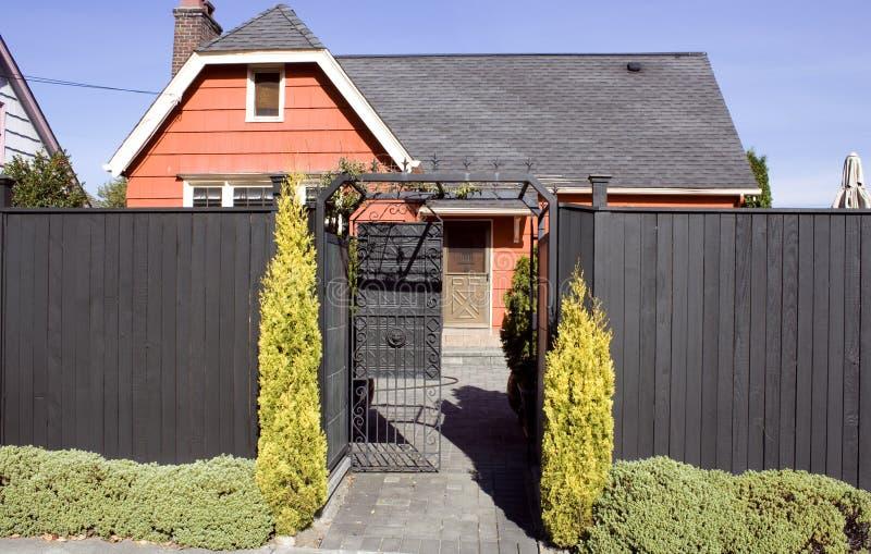 Vieille maison orange avec la haute frontière de sécurité image libre de droits