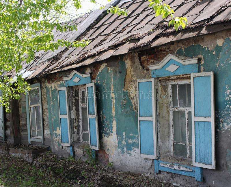 Vieille maison ruinée avec des volets de fenêtre ouverte dans le village en été photos stock
