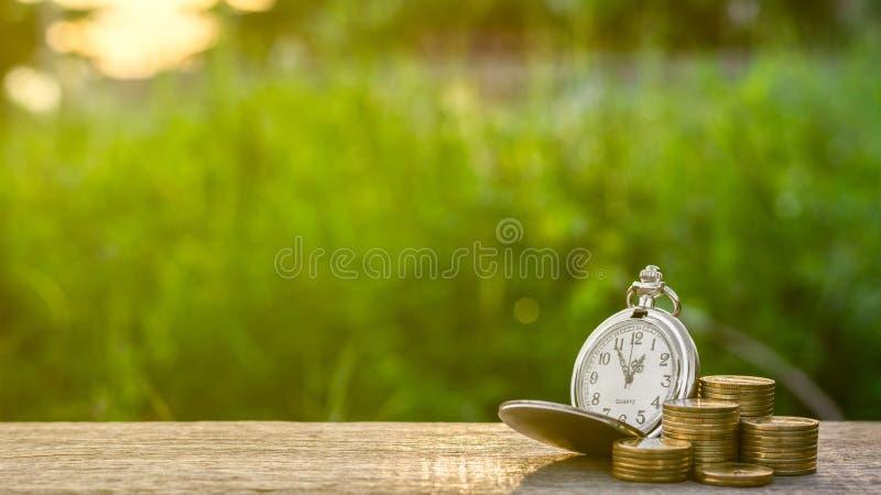 Vieille montre de poche et une pile de pièces de monnaie d'or sur la table photos stock