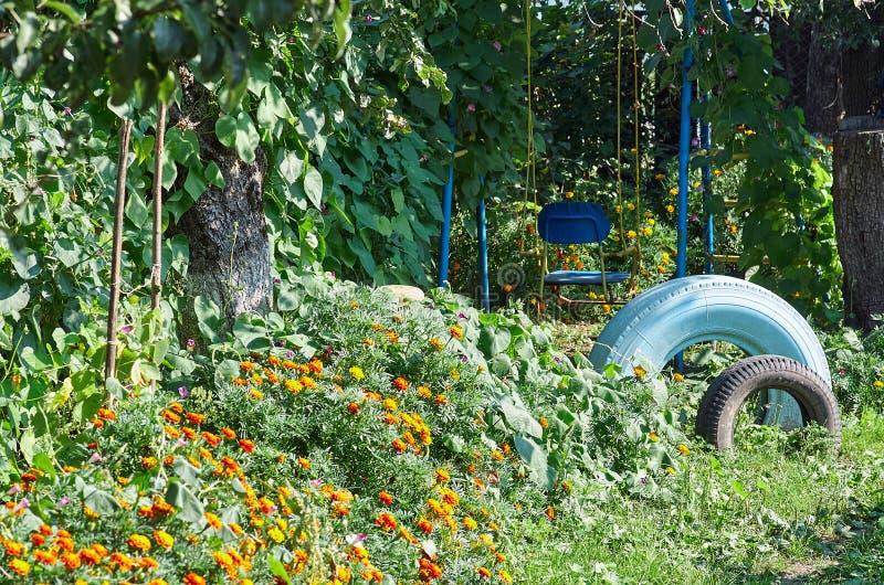 Vieille oscillation entre les fleurs dans un jardin avec for Fleurs dans un jardin