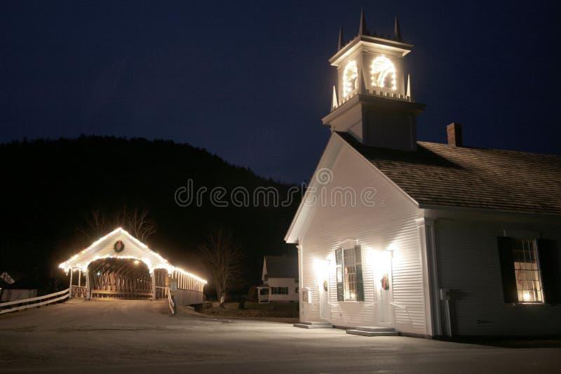 Vieille passerelle couverte de la Nouvelle Angleterre avec l'église la nuit images stock