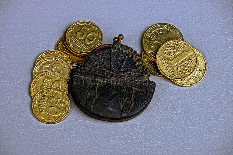 Vieille petite bourse et pièces de monnaie jaunes sur la table images libres de droits