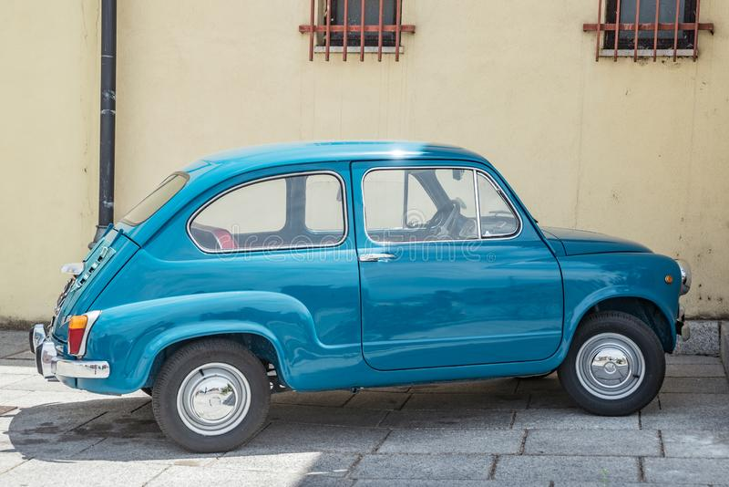 Vieille, petite, italienne voiture : Fiat 600 en état parfait Fond jaune photo stock