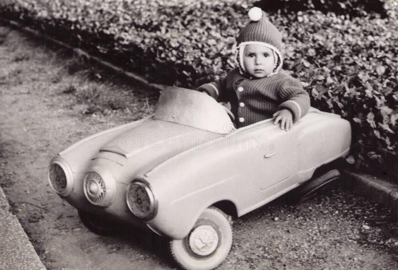 Vieille photographie d'une petite fille dans une voiture de jouet photos libres de droits