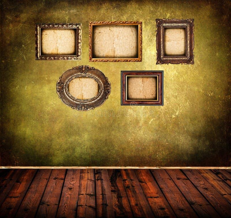 Vieille pièce avec les cadres grunges de mur et de cru photo stock
