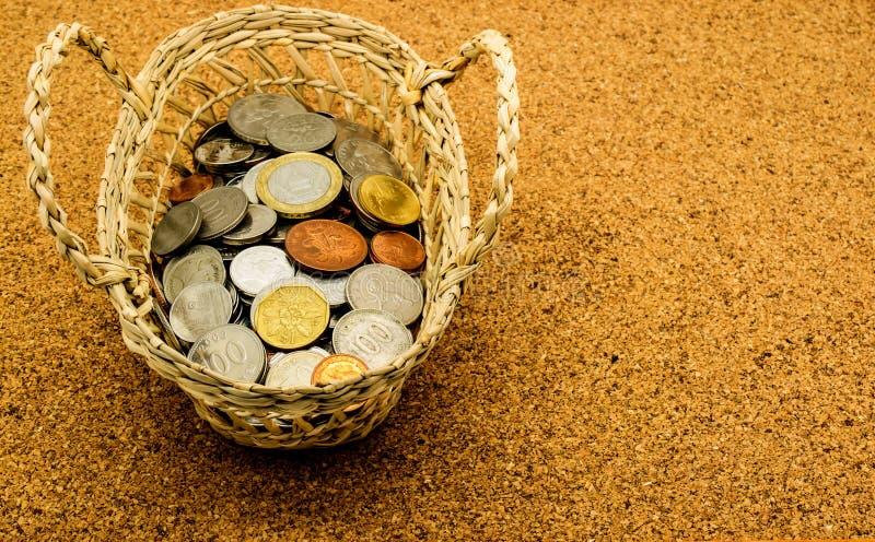 Vieille pièce de monnaie internationale dans le panier sur le panneau de liège image libre de droits