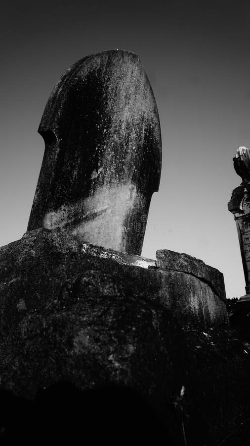 Vieille pierre tombale superficielle par les agents et portée au cimetière photographie stock libre de droits