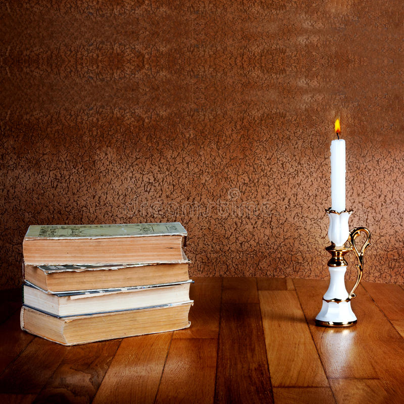 Vieille pile de livres avec le chandelier et la bougie brûlante images libres de droits