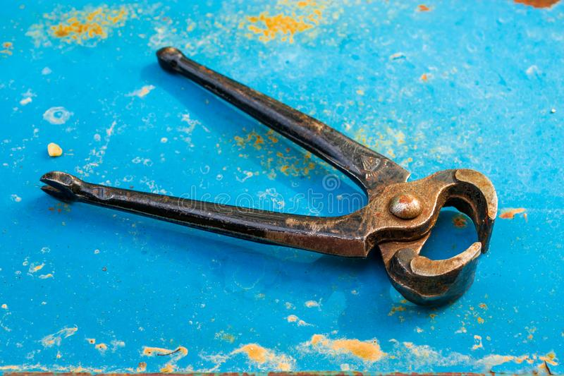 Vieille pince rouillée sur un fond bleu et rouillé en métal Les leviers de première classe ont employé principalement pour enleve photos stock