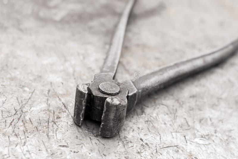 Vieille pince sur un établi en métal photographie stock libre de droits