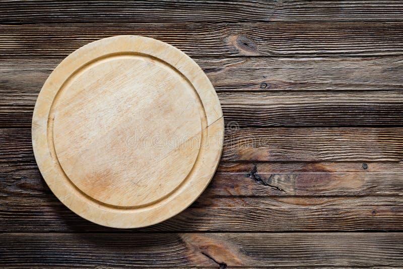 Vieille planche à découper en bois ronde sur la table en bois images libres de droits