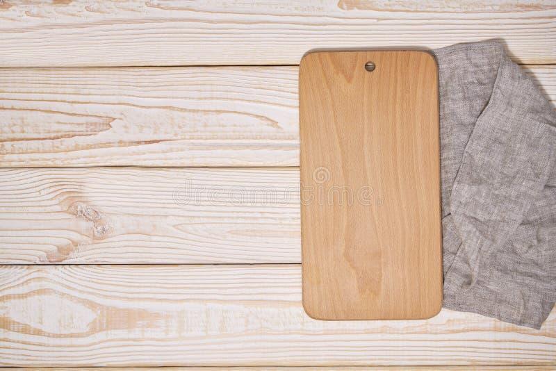 Vieille planche à découper en bois vide sur le fond en bois blanc, vue supérieure photo libre de droits