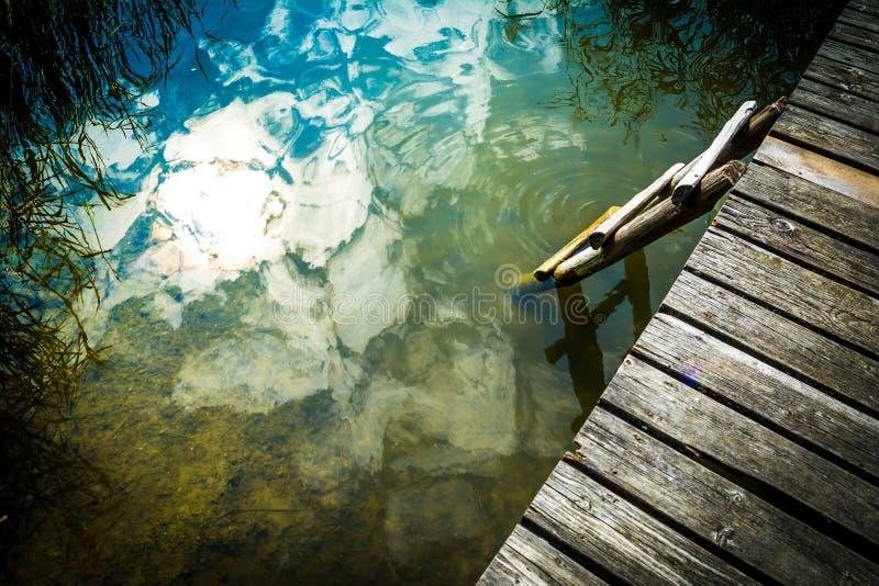 Vieille plate-forme en bois sur le lac avec une échelle dans l'eau donnant sur les roseaux contre le ciel bleu un jour ensoleillé photographie stock