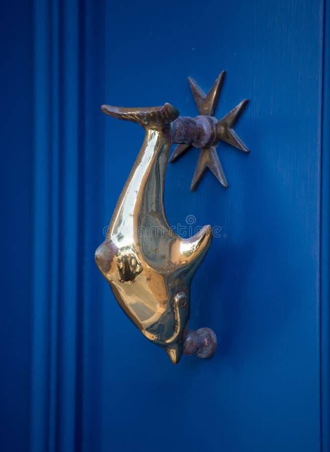 Vieille poignée de dauphin de porte avec la croix maltaise sur la porte bleue, La Valette, Malte photo stock