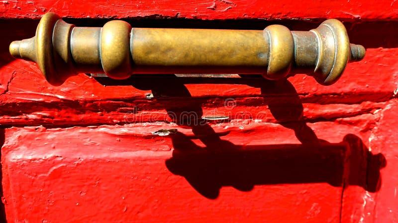 Vieille poignée en laiton sur la porte en bois rouge photo libre de droits