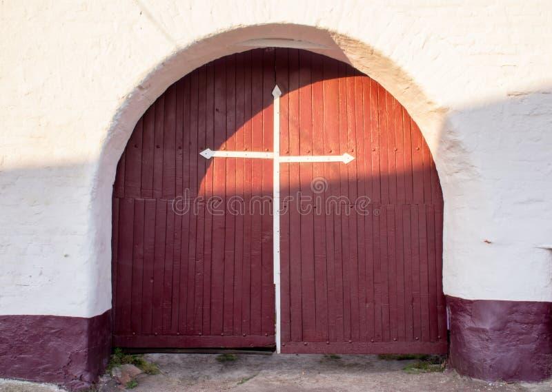 Vieille porte antique de porte de rouge foncé d'entrée avec une croix blanche sur eux contre un mur de briques blanc solide Entré photographie stock libre de droits