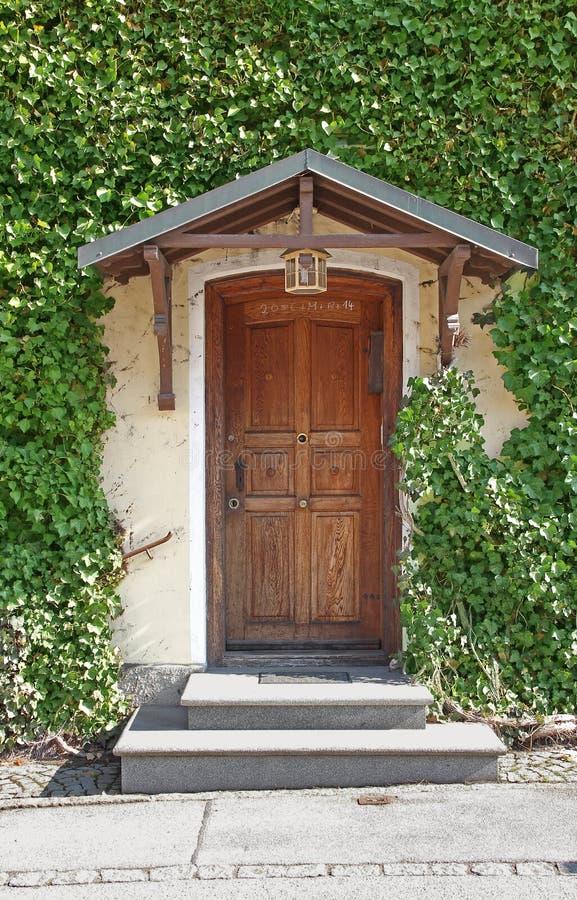 Vieille porte couverte et avant envahi de maison image libre de droits
