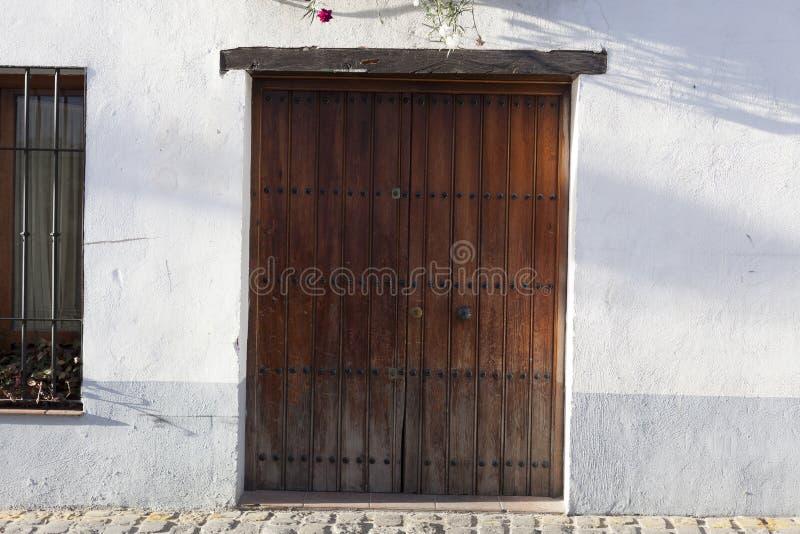 Vieille porte découpée superficielle par les agents, mur blanc images stock