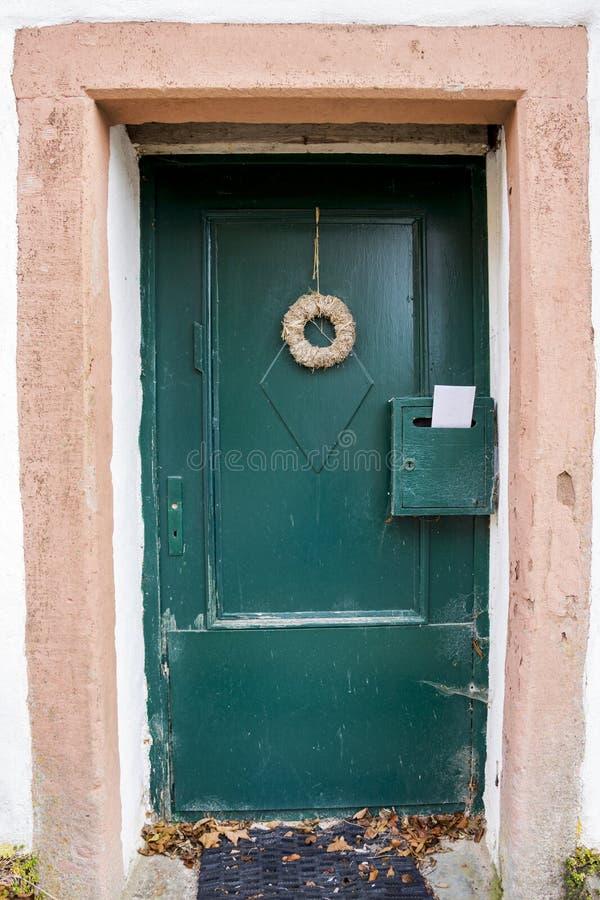 Vieille porte d'entrée d'une maison allemande abandonnée, des toiles d'araignée, d'une guirlande décorative et d'une lettre dans  photographie stock libre de droits