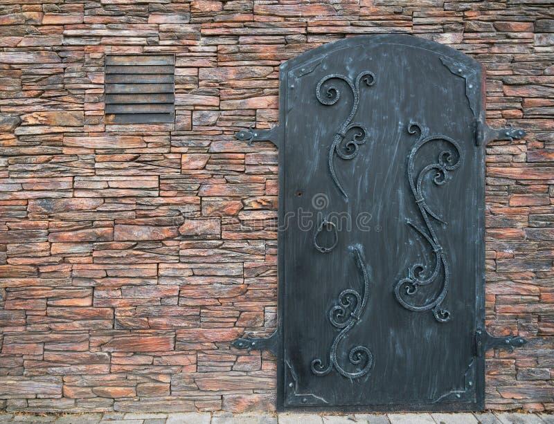 Vieille porte de fer avec un mur en pierre image libre de droits
