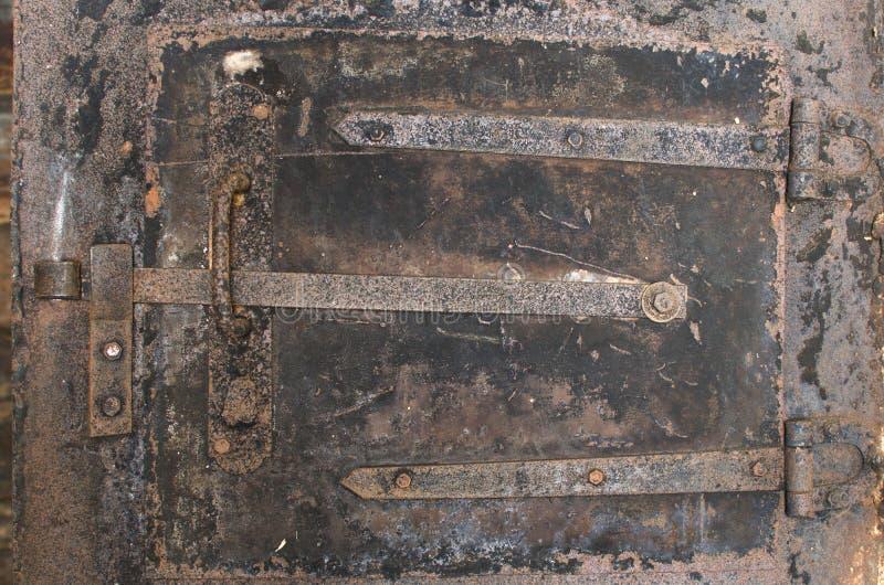 Vieille porte de four de fer avec un boulon rouillé photos stock