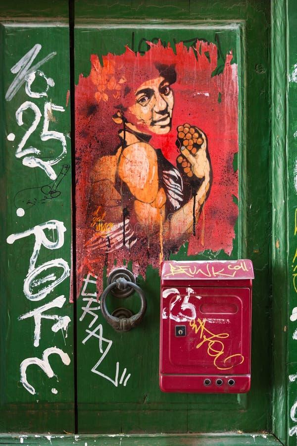 Vieille porte en bois couverte de graffiti dans le secteur de Trastevere Rome, photographie stock libre de droits