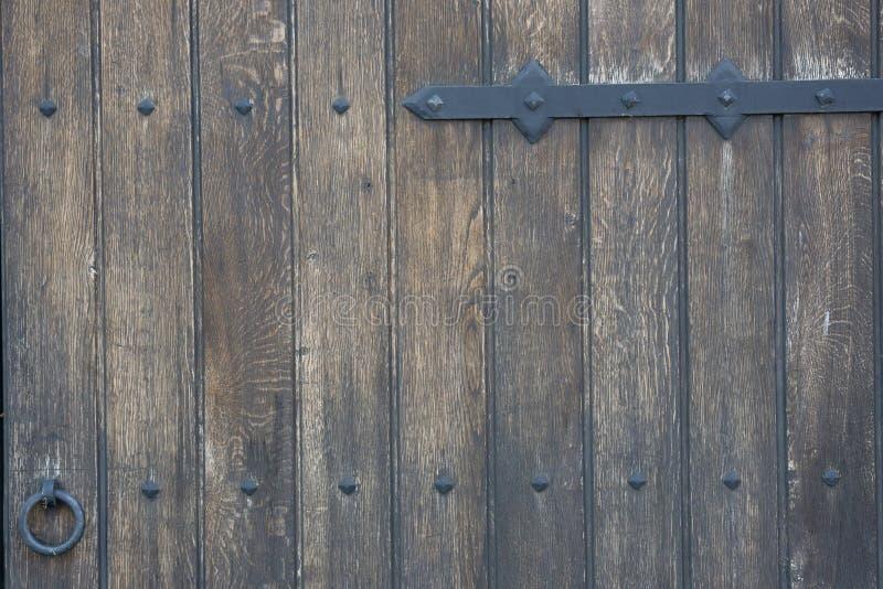 Vieille porte en bois dans le mur en pierre de l'ère médiévale Cadenas en métal de cru sur une porte en bois images libres de droits