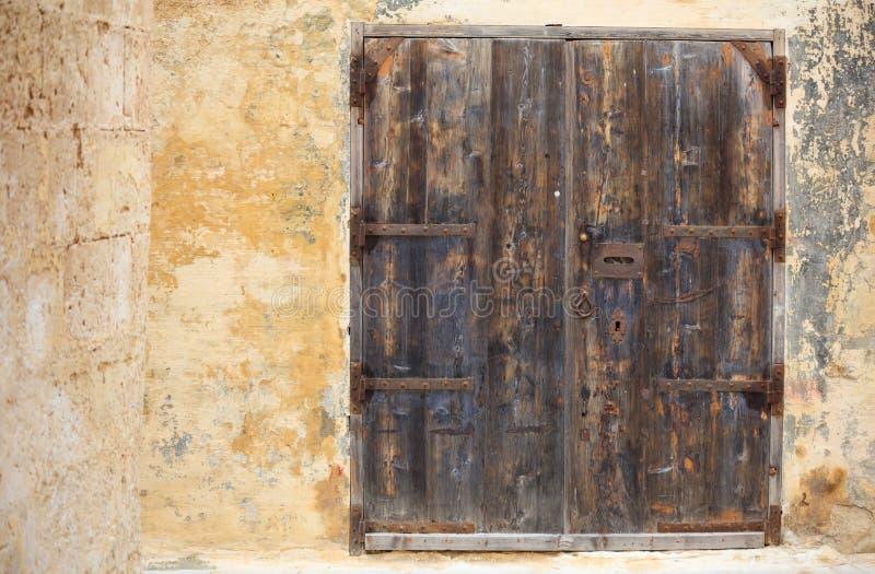 Vieille porte en bois fermée avec l'ouverture rouillée de boîte aux lettres en métal et détails, l'espace pour le texte Mdina, Ma photos libres de droits