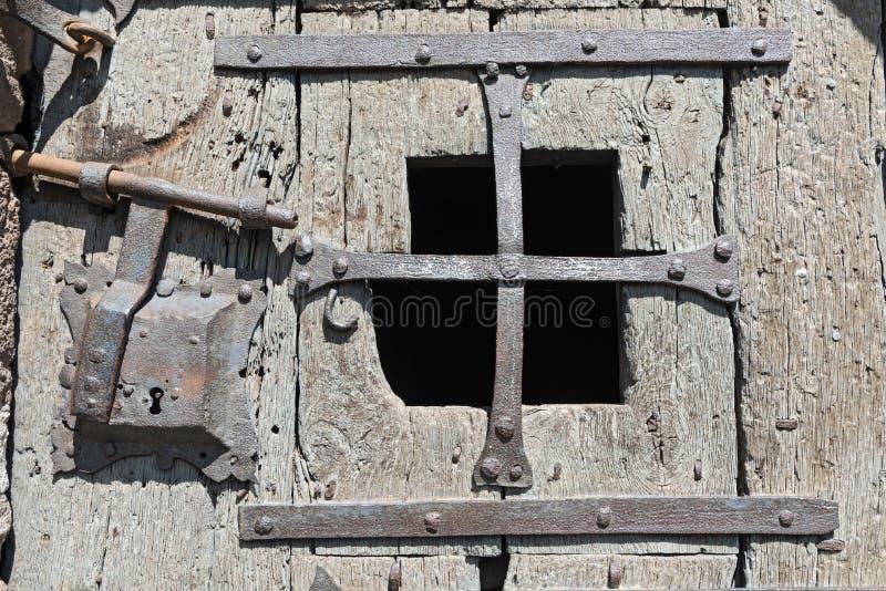 Vieille porte en bois médiévale avec des garnitures de fenêtre et de fer travaillé photographie stock libre de droits